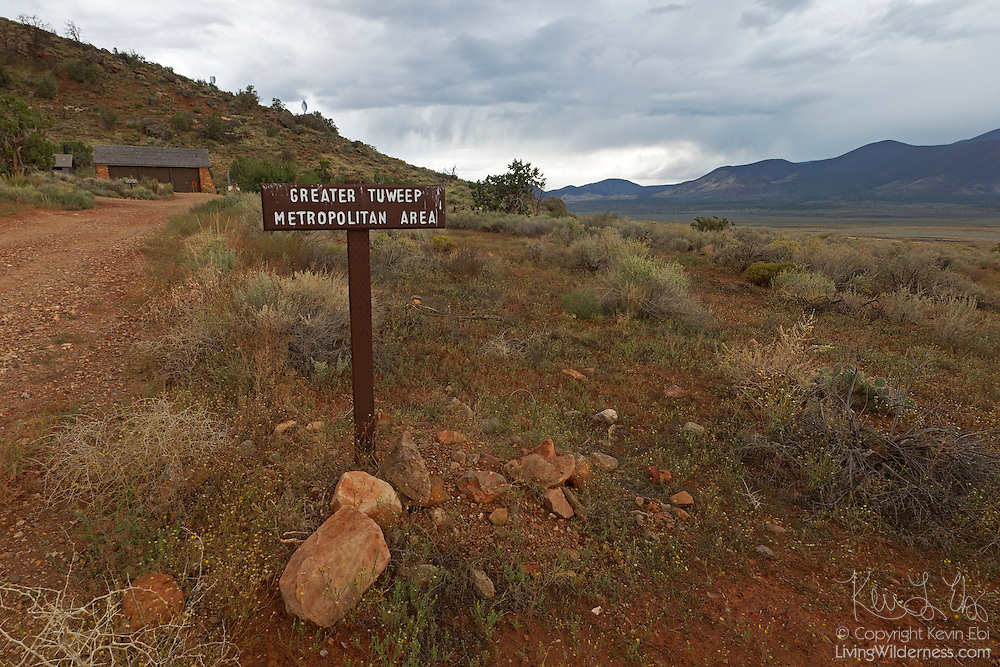 "A sign reading ""Greater Tuweep Metropolitan Area"" welcomes travelers to the Tuweep, or Toroweap, section of Grand Canyon National Park in Arizona. The ""metropolitan area"" consists of a ranger's house, a maintenance shed and a vault toilet."