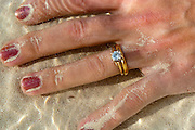 A woman holds her hand underwater on a warm sandy beach, her diamond ring glistening in the sun.