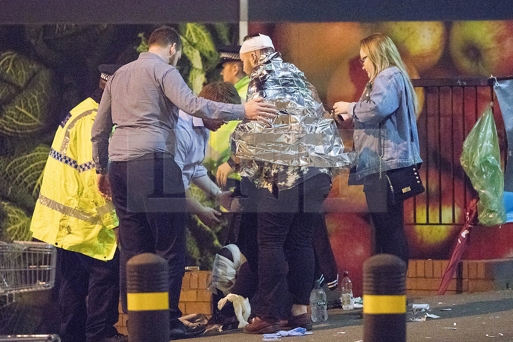 © Licensed to London News Pictures . FILE PICTURE DATED 22/05/2017 as Manchester prepares to mark a year since the Manchester Arena terror attack . Manchester, UK. Walking wounded on Corporation Street , opposite Victoria Station . Police and other emergency services are seen near the Manchester Arena after Salman Abedi murdered 22 and injured dozens more at an Ariana Grande concert at Manchester Arena. Photo credit : Joel Goodman/LNP