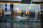 Reflected retail advertising poster and parked aircraft at Heathrow's Terminal 5.