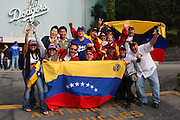 LOS ANGELES, CA - MARCH 21: Three fans of Korea appear overwhelmed by fans of Venezuela waving flags and cheering before game one of the semifinal round of the 2009 World Baseball Classic at Dodger Stadium in Los Angeles, California on Saturday March 21, 2009. Korea defeated Venezuela 10-2. (Photo by Paul Spinelli/WBCI/MLB Photos)