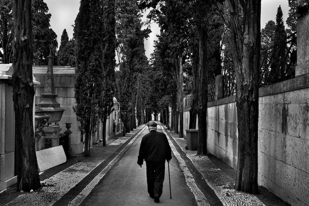 An elderly walks down an alley inside a cemetery after praying for a relative during the All Souls Day (one of four holidays that cease from 2013 due to austerity measures), in Lisbon, Portugal, on November 1, 2012. Portugal is on the top EU country list in inequality and social contrast. Poverty rates on elderly community is nowadays in 21%, and Lisbon itself has increased 80% over the past 20 years. Due to the financial crisis, the number of retired people on food distribution centers increases weekly while austerity measures recently announced by the government has affected dozens of social institutions. Data released on Sunday by the WHO (World Health Organization) indicates that 39.4% of elderly people in Portugal are victims of abuse and, of these, 32.9% are victims of psychological abuse, 16.5% of racketeering, 12.8% of violation of their rights, 9.9% of negligence, 3.6% of sexual abuse and 2.8% of physical abuse. Still, from a WHO research, in Portugal, 44% of households with a person aged over 65 years have financial difficulties in keeping the home adequately heated. Photo by Mauricio Lima for The New York Times