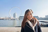 Portrait of happy young woman standing against London Eye at London; England; UK