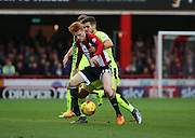 Brentford midfielder Ryan Woods holding Huddersfield Town defender Tommy Smith off the ball during the Sky Bet Championship match between Brentford and Huddersfield Town at Griffin Park, London, England on 19 December 2015. Photo by Matthew Redman.