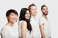 Side view of young multi-ethnic friends in casuals smiling over white background