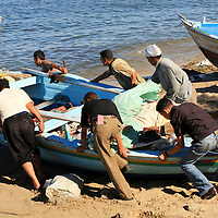 Unity is strength. Group of men pushing a fishing boat into the sea, Alexandria, Egypt