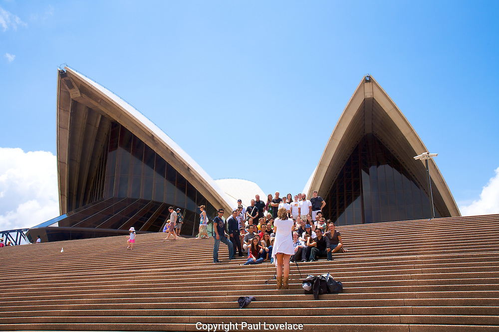 Tourists have a group portrait taken on the steps of the Opera House, Sydney..Paul Lovelace Photography 16.01.11