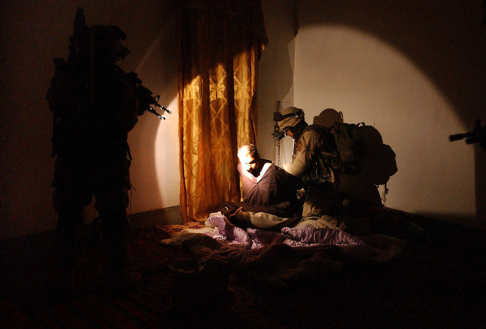 DETAINED.Soldiers from Charlie Company, 5th Battalion, 20th Infantry Regiment, 3rd Brigade, 2nd ID, detain an iraqi man during raid on a complex of houses in Ad Duluiyah, Iraq, which they believed was being used as a recruiting site for gurrilla fighters for a terrorist group, known as Army of Mohamad. Eight men were detained in the early morning raid on December 23, 2003.  (Alan Lessig/Army Times)