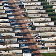 "A man camp outside of Williston, North Dakota.  The oil boom has brought unprecedented prosperity to little towns like Watford City, N.D. (population 1,744), it has also exacerbated problems in housing, infrastructure and traffic...Williston (""Kuwait on the Prairie""), Watford City and their neighboring towns in North Dakota sit atop the biggest lake of oil to be discovered in North America since Alaska's Prudhoe Bay in 1968. ..There are too many unfilled jobs and not enough empty beds to accommodate the masses of people looking for work in the oil boom, man camps have sprung up throughout the formerly idyllic  prairie. They are dormitory-style buildings, FEMA trailers, or RV's, and a temporary solution to housing workers but are straining utilities and stretching towns emergency services."