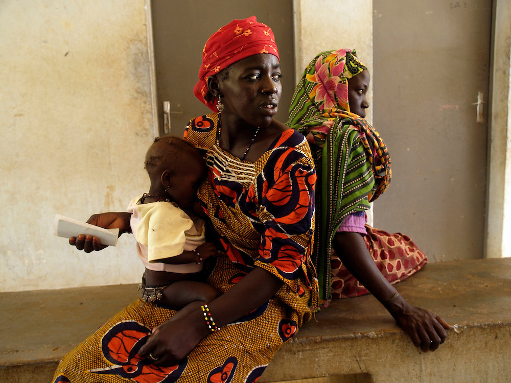 In Yawouri clinic in Niger a mother with her malaria ill baby daughter wait for the nurses in the dirty corridor.