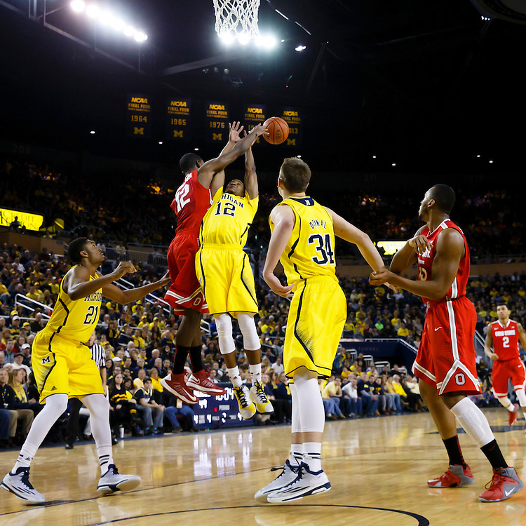 Feb 22, 2015; Ann Arbor, MI, USA; Ohio State Buckeyes forward Sam Thompson (12) knocks the ball back on the rebound over Michigan Wolverines guard Muhammad-Ali Abdur-Rahkman (12) in the second half at Crisler Center. Michigan won 64-57. Mandatory Credit: Rick Osentoski-USA TODAY Sports