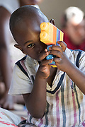 Lusaka, Zambia - 20.04.18  - Jackson plays with his 'camera' made of blocks at a Cheshire CBR program in Chipata Compound in Lusaka, Zambia, on April 20, 2018.  Jackson had yellow fever as a newborn and was delayed in walking, says his grandmother.