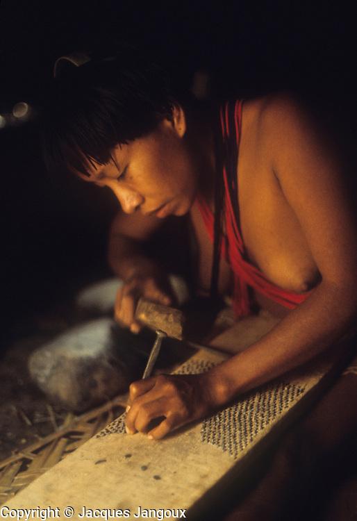 Piaroa (Wõthĩhã, Wo'tiheh, Wothuha, Wötïhä) Indians: woman inserting small stones on board to make manioc grater. South America, Venezuela, Guiana Highlands.