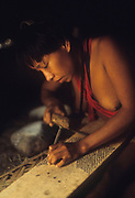 Piaroa (Wõthĩhã, Wo'tiheh, Wothuha, Wötïhä) Indians: woman inserting small stones on board to make manioc grater. South America, Venezuela, Guiana Highlands.
