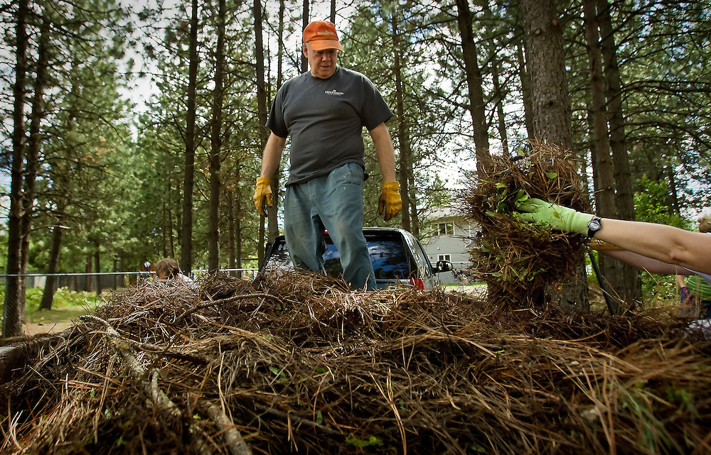 Wayne Stephens waits for more piles of pine needles to be dumped in his trailer so he can compact them Friday at Children's Village in Coeur d'Alene during the Windermere Community Service Day.