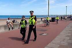 Portobello, Scotland, UK. 26 May 2020. Portobello beach and promenade were relatively quiet despite sunny warm weather. Police patrols on foot were low key and officers were not asking many members of the public to move on.  Iain Masterton/Alamy Live News