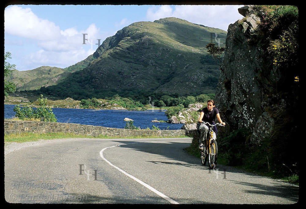 Teenage girl pedals rental bike up road past Upper Lake in Killarney National Park, Ireland.
