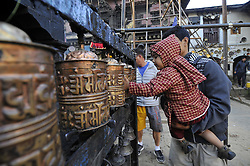 October 19, 2016 - Kathmandu, NP, Nepal - A Kid helps by his father to rotate ritual prayer wheel at the premises of Adinath Temple during a month Adinath Mela festival in Chobhar, Kirtipur, Kathmandu, Nepal on Wednesday, October 19, 2016. In the month of October or November from Kojagrat purnima to Kartik purnima for a month, people visit Adinath temple in the morning and perform special rituals puja and ritual function during Adinath Mela. (Credit Image: © Narayan Maharjan/NurPhoto via ZUMA Press)
