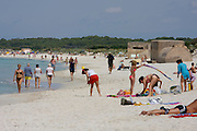 Tourists and bunkers on the white sand beach at Es Trenc.