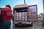 Huixcolotla, Mexico – March 27, 2017: A man sells stolen gasoline inside of a wholesale market.