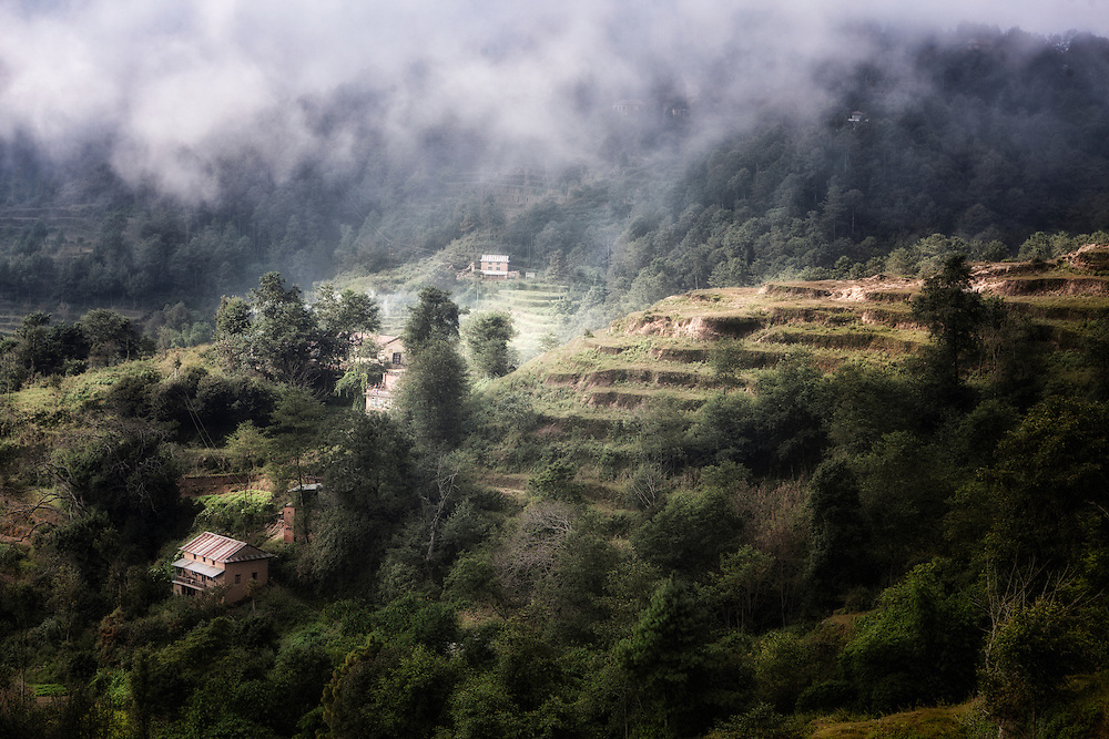 A terraced hillside in Nepal on a foggy morning.