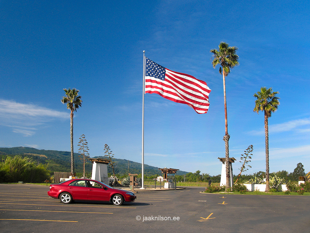 American flag flying in Calistoga, Napa Valley, California, USA. Parking lot with car.