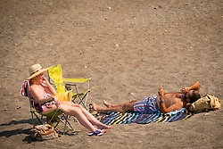 © Licensed to London News Pictures. 05/07/2018. Aberystwyth, UK.  A couple relax on the beach at mid-morning in Aberystwyth at the start of what promises to be yet another hot and almost cloudless day, as the prolonged heatwave continues to dominate the weather over the UK. Photo credit Keith Morris/LNP
