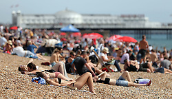 Embargoed to 0001 Monday April 30 File photo 26/08/17 of people sun bathing on Brighton Beach in Sussex. Research by hotel chain Travelodge showed that almost three out of five people will have their annual summer break in this country, up by 2\% on last year.