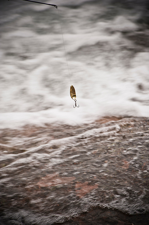 Shorecasting for trout and salmon on Lake Superior near Marquette Michigan in fall autumn.