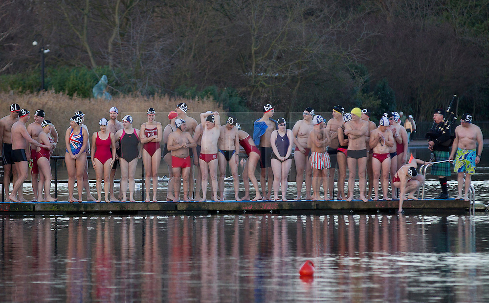 © Licensed to London News Pictures. 25/12/2013. London, UK. Members of the Serpentine Swimming Club stand on a jetty as they prepare to take part in the Serpentine Swimming Club's annual Christmas morning 'Peter Pan Cup' race in Hyde Park, London, today (25/12/2013). The race, which takes place every Christmas Day on the Serpentine River, takes its name from from the novel by J.M.Barrie after the author presented the first Peter Pan Cup in 1904. Photo credit: Matt Cetti-Roberts/LNP
