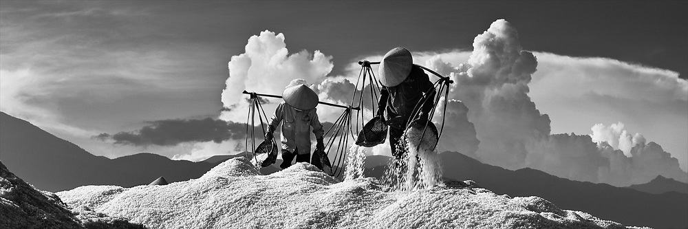 Two women collecting salt at the salt field in Nha Trang city -Middle of Viet Nam