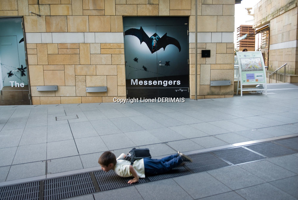 A boy plays in Roppongi Hills in front of a poster for Annette Messager's Tokyo show, Tokyo, Japan.