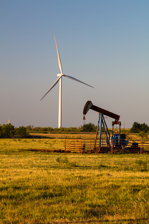 Pumpjack in a rural Texas field with wind turbine on the horizon at dusk.