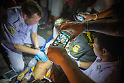 "10 NOVEMBER 2012 - BANGKOK, THAILAND: A passerby uses a smart phone to photograph a Ruamkatanyu Foundation medical team trying to save the life of a boy hit by a vehicle near the Klong Toey slum in Bangkok. The child had severe head injuries and died at the scene. The Ruamkatanyu Foundation was started more than 60 years ago as a charitable organisation that collected the dead and transported them to the nearest facility. Crews sometimes found that the person they had been called to collect wasn't dead, and they were called upon to provide emergency medical care. That's how the foundation medical and rescue service was started. The foundation has 7,000 volunteers nationwide and along with the larger Poh Teck Tung Foundation, is one of the two largest rescue services in the country. The volunteer crews were once dubbed Bangkok's ""Body Snatchers"" but they do much more than that now.    PHOTO BY JACK KURTZ"