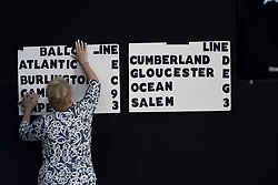 Campaign volunteer Helen Duda mounts a board  indicating the candidate's position on the eight different ballots for the upcoming Primaries.
