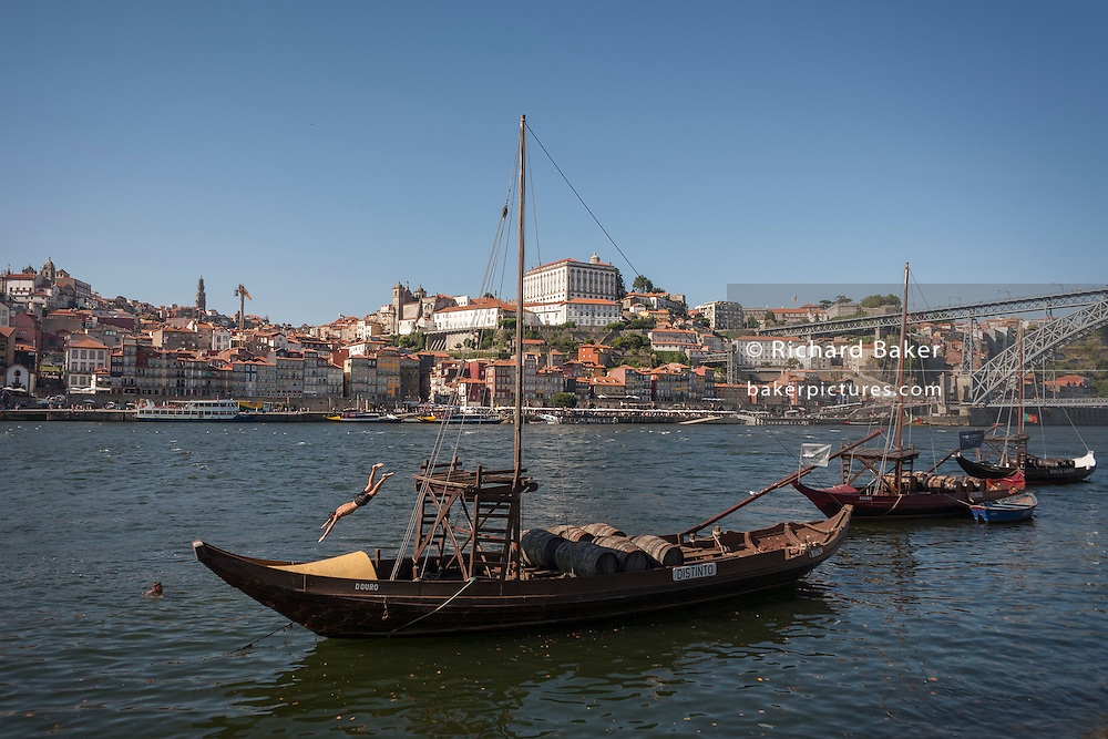 Local youth dives off a traditional Rabelo boat (Port wine transporter), into the River Douro in Porto, Portugal.