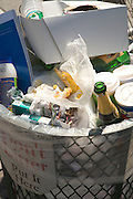 a street side garbage can filled to the top with bottles and various other trash