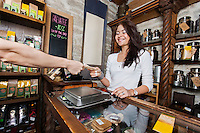 Smiling young salesperson accepting money from customer in tea store