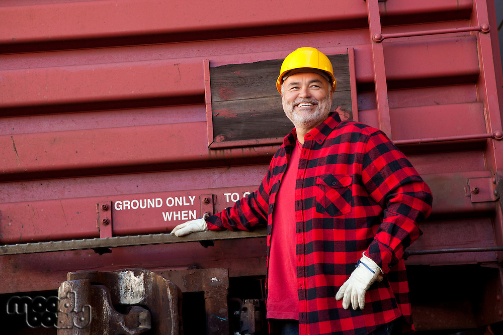 Middle Aged worker standing in industrial railway carriage