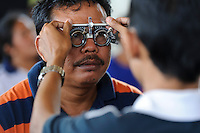 A man having his sight tested prior to being given free corrective glasses, Bali Indonesia.