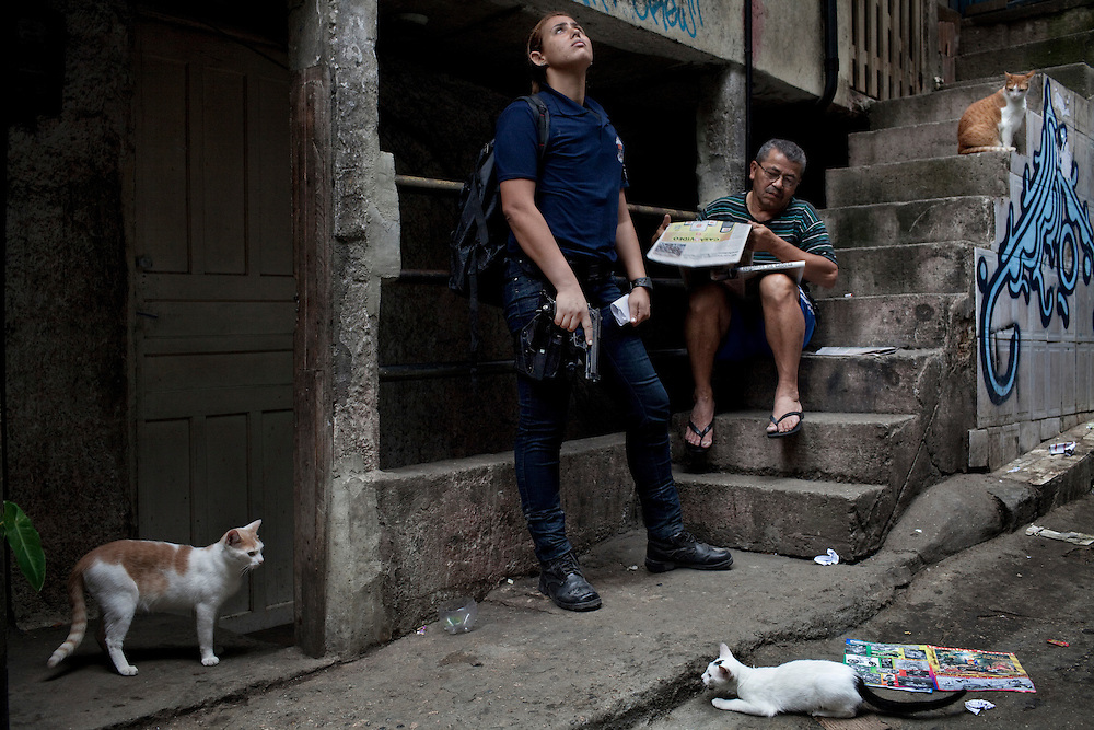A resident reads a newspaper a female police member of special forces patrols nearby during an incursion by security forces into 'Rocinha', one of Brazil's biggest slums controlled by drug traffickers, on November 13, 2011, Rio de Janeiro, Brazil. Photo by Mauricio Lima for The New York Times