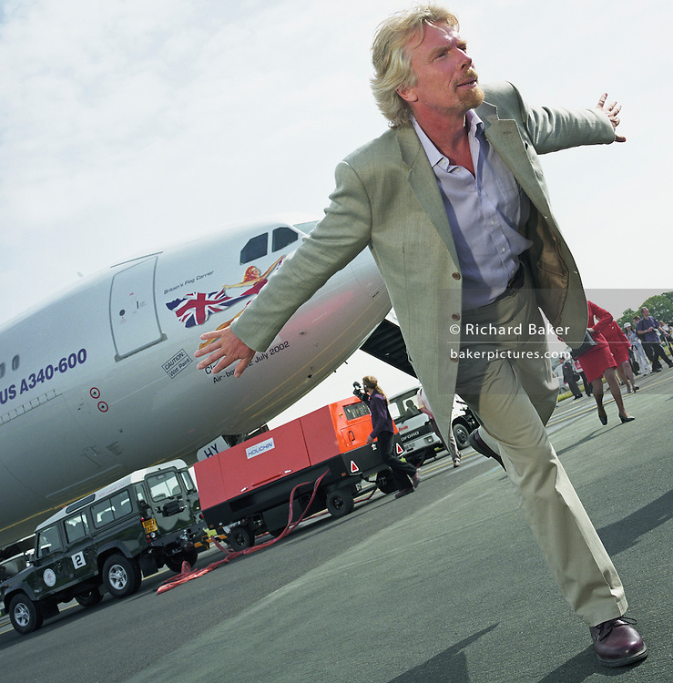Virgin Chairman Sir Richard Branson performs in front of the media during a publicity launch of Virgin Atlantic's new Airbus A340-600 which is parked behind the business tycoon during the Farnborough Air Show in Hampshire, England. He stands on one leg in a typically eccentric aviation-owner balancing trick. Behind him near the aircraft's nose a Virgin 'babe' echoes his outstretched arms while flying the British Union Jack flag. Farnborough centres its presence on big aerospace business to the tune of $40bn in orders and industry leaders like Branson, Boeing and Airbus parade their brands and announce new orders throughout the week-long display. Picture from the 'Plane Pictures' project, a celebration of aviation aesthetics and flying culture, 100 years after the Wright brothers first 12 seconds/120 feet powered flight at Kitty Hawk,1903. .
