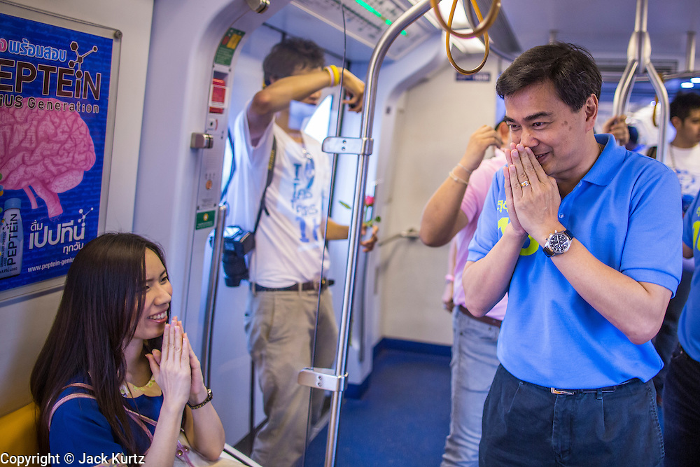 16 FEBRUARY 2013 - BANGKOK, THAILAND:  ABHISIT VEJJAJIVA, former Prime Minister of Thailand, greets voters on the BTS Skytrain while he campaigns for his party colleague Sukhumbhand Paribatra ahead of Bangkok's governor election. Bangkok residents go to the polls on March 3 to elect a new governor. Sukhumbhand Paribatra, the current governor, is running on the Democrat's ticket and is getting help from national politicians like Abhisit Vejjajiva, the former Thai Prime Minister. One of Sukhumbhand's campaign pledges is to improve Bangkok's mass transit and transportation system. Abhisist road the BTS Skytrain to campaign for Sukhumbhand.     PHOTO BY JACK KURTZ