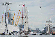 The Loth Lorien passes the O2 - Royal Greenwich Tall Ships Festival with a fleet of square rigged ships moored on the Thames at Greenwich and Woolwich. The fleet includes two of the biggest Class A Tall Ships - the Dar Mlodziezy and Santa Maria Manuela - which are moored on Tall Ships Island in the river off Greenwich. Tall Ships Festival Day on Saturday 29 August featured free family entertainment and the chance to enjoy a taste of life on the high seas.
