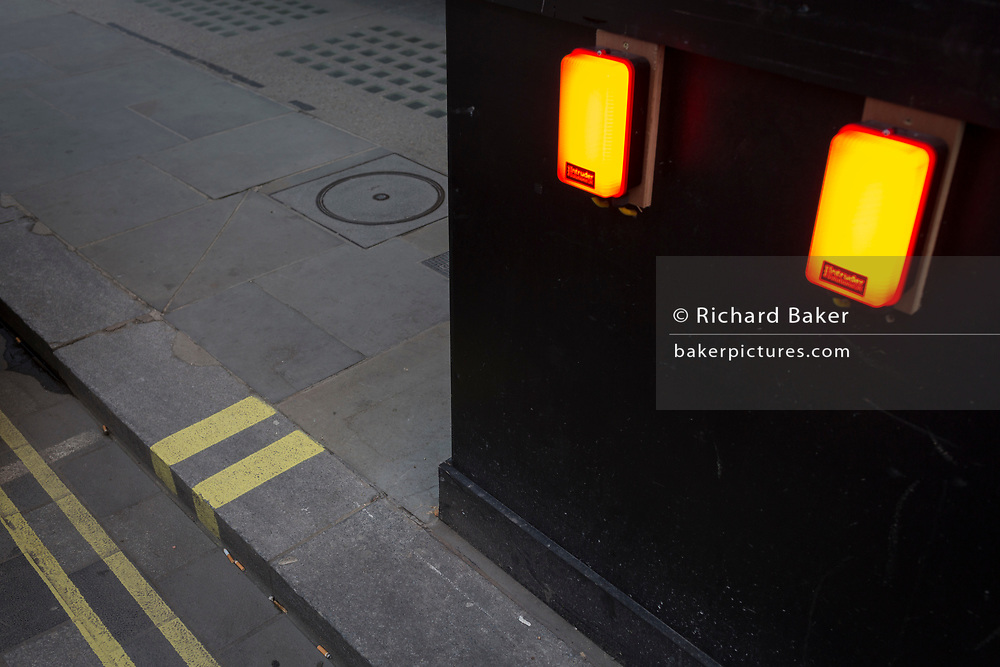 The repetition of twin construction hoarding lights and parallel yellow lines on the kerb and in the gutter of a Soho street, on 6th February 2018, in London, England.