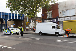 © Licensed to London News Pictures. 08/08/2019. London, UK.  Police and workers prepare to move a van at the scene in Leyton this morning in Leyton High Road, where a police officer has been left in a critical condition after being stabbed repeatedly whilst attempting to stop a van in east London. The injured Police Officer, believed to be aged in his thirties, was rushed to hospital and is in a critical but stable condition..  Photo credit: Vickie Flores/LNP
