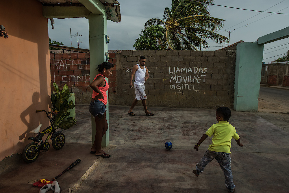 "LA VELA, VENEZUELA - SEPTEMBER 11, 2016:  Roymar Bello plays with her son, husband and niece, trying to make the most out of her last weekend at home before leaving the country to work undocumented in Aruba. Despite having the largest known oil reserves in the world, Venezuela is suffering from hyperinflation and a severe economic crisis making affordable food difficult for most middle and working class families to access.  Well over 150,000 Venezuelans have fled the country in the last year alone, the highest in more than a decade, according to scholars studying the exodus. As Hugo Chávez's Socialist-inspired revolution collapses into economic ruin, as food and medicine slip further out of reach, the new migrants include the same impoverished people that Venezuela's policies were supposed to help. ""We have seen a great acceleration,"" said Tomás Paez, a professor who studies immigration at the Central University of Venezuela. He says that as many as 200,000 Venezuelans have left in the last year, driven by how much harder it is to get food, work and medicine — not to mention the crime such scarcities have fueled.  PHOTO: Meridith Kohut for The New York Times"