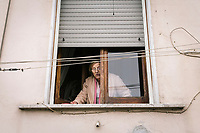 """NAPLES, ITALY - 2 FEBRUARY 2019: An elderly woman living in the Rione Luzzatti, the neighborhood in which Elena Ferrante's """"My Brilliant Friend"""" is set,  chats with passengers of the literary bus tour """"Neapolitan Novels"""" in Naples, Italy, on February 2nd 2019.<br /> <br /> In December 2018, City Sightseeing - the world's largest sightseeing tour bus operator - inaugurated the """"Brilliant Naples"""" tour, inspired by the locations in """"Neapolitan Novels"""", a 4-part series by the Italian novelist Elena Ferrante. The series has sold over 10 million copies in 40 countries. The first book in the series has also been adapted into an HBO television series entitled, """"My Brilliant Friend."""""""