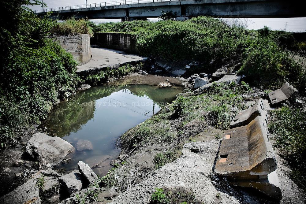 UN CANALE DI SUPPORTO PER LE ESONDAZIONI COMPLETAMENTE OSTRUITO DAI RIFIUTI SVERSATI AL SUO INTERNO
