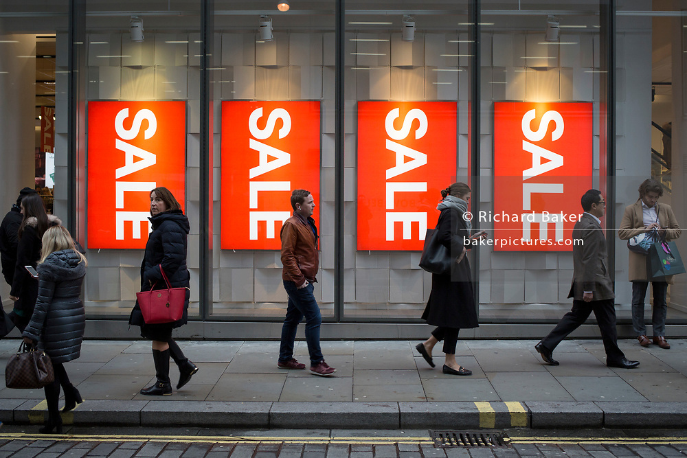 Shoppers walk past Christmas Sale signs outside the H&M branch of H&M in the City of London, the capital's financial district, on 19th December 2018, in London UK.